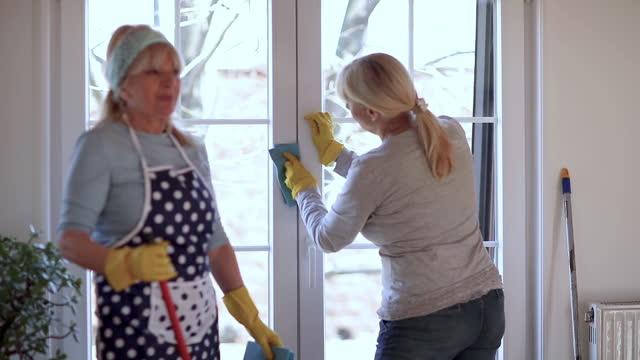 vídeos y material grabado en eventos de stock de amigas mayores limpiando ventanas en apartamento - cinta de cabeza