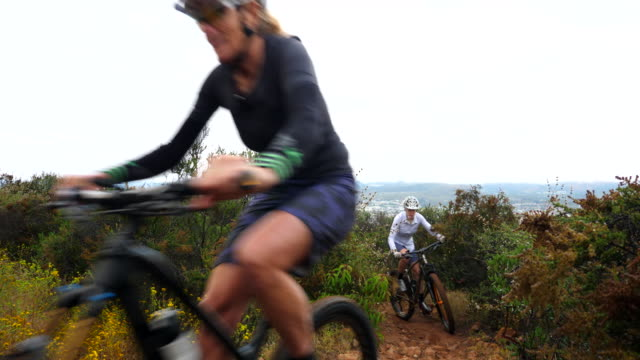 ms senior female friends climbing hill on mountain bike during early morning ride - mountain bike stock videos & royalty-free footage