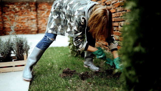 Senior female gardener working in her garden