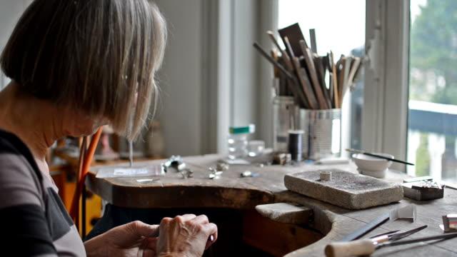 Senior female jeweler working on a ring