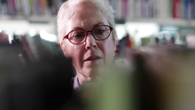 senior female looking for a book in library - library stock videos & royalty-free footage