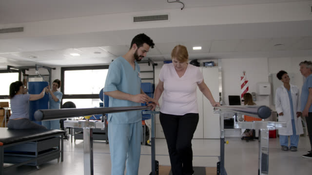 senior female patient assisted by her male therapist walking with the support of parallel bars during therapy - medical scrubs stock videos & royalty-free footage