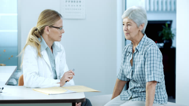 Senior female patient explaining symptoms to her female physician