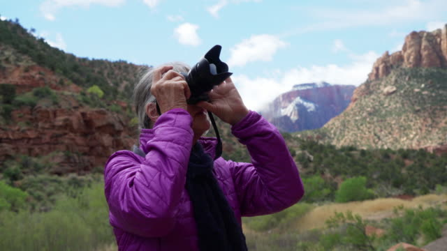 senior female photographer taking pictures of sandstone canyon in zion utah - sandstone stock videos & royalty-free footage