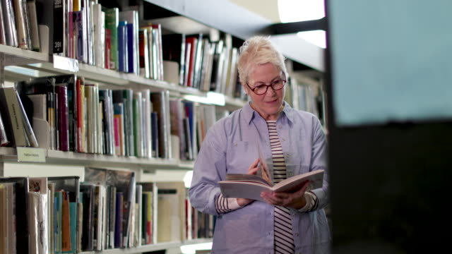 Senior female reading a book in library