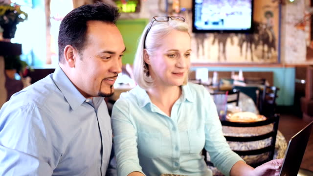 senior female restaurant owner meeting with hispanic male manager in dining room - mexican restaurant stock videos & royalty-free footage