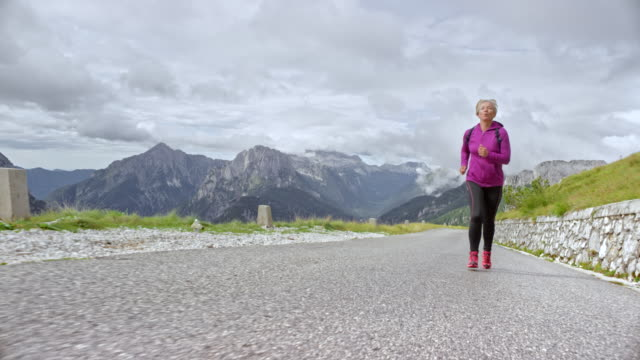 SLO MO Senior female runner ascending a high mountain road with beautiful mountain peaks in the background