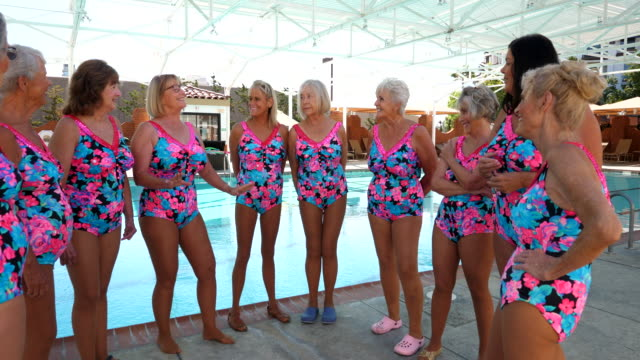 ms senior female synchronized swim team listening to teammates story while standing on pool deck - 60 69 years stock videos & royalty-free footage