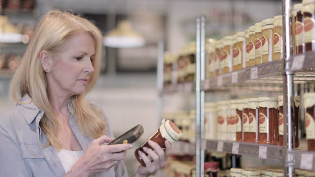 senior female using self scan in a grocery store - jam stock videos & royalty-free footage