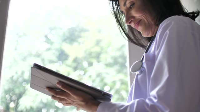 vídeos de stock e filmes b-roll de senior female woman doctor using tablet pc, slow motion - profissional de enfermagem