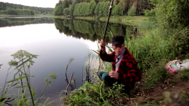 Senior fisherman catching fish in river