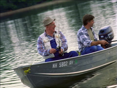 canted senior fisherman in hat pulling fishing rod + talking to man steering boat on lake - adult offspring stock videos & royalty-free footage