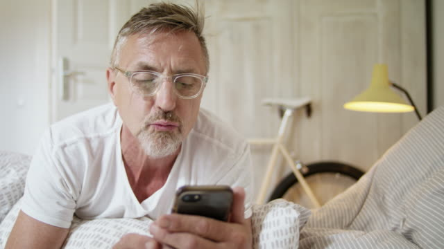 senior fit and healthy man in his early 60s with short greying hair and grey beard in his stylish bedroom does a video call. - portable information device stock videos & royalty-free footage