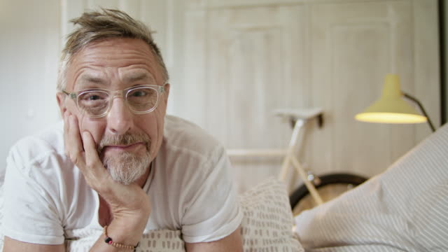 vidéos et rushes de senior fit and healthy man in his early 60s with short greying hair and grey beard in his stylish bedroom looking at camera smiling and posing for partner portal. - prise de vue en intérieur