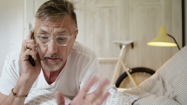 senior fit and healthy man in his early 60s with short greying hair and grey beard in his stylish bedroom doing an unpleasant phone call. - alterungsprozess stock-videos und b-roll-filmmaterial