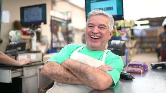 fioraio anziano come cassiere in un piccolo negozio di fiori - mercante video stock e b–roll