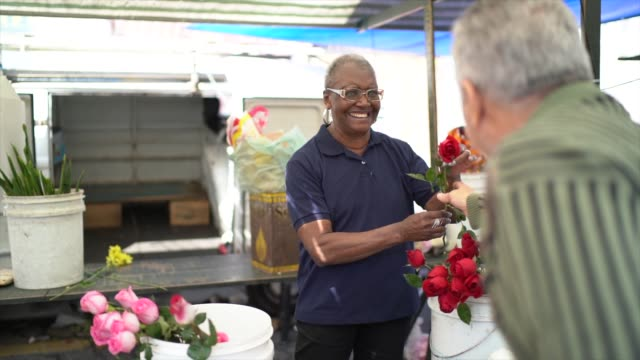 senior florist selling a rose to client - flower shop stock videos & royalty-free footage