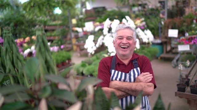 vidéos et rushes de fleuriste aîné restant avec des bras croisés - jardiner