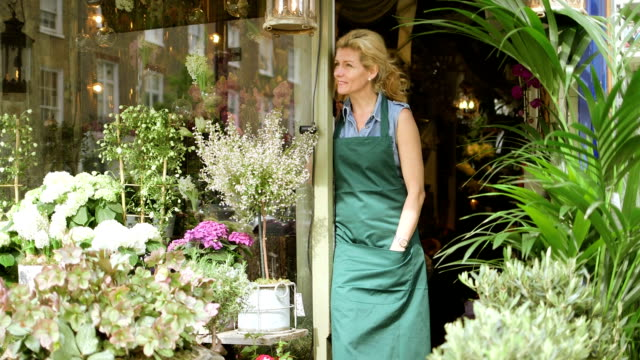 mls a senior florist stands in the doorway of her shop proudly admiring her flowers - fioraio negozio video stock e b–roll
