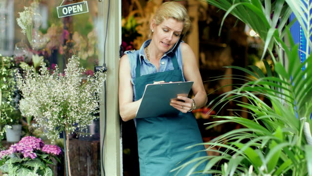 MLS Senior Florist stands in the doorway of shop, making a business call
