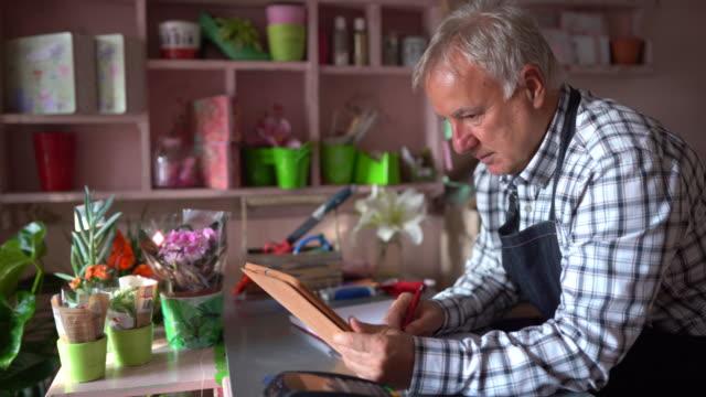 vidéos et rushes de fleuriste aîné utilisant la tablette numérique à la boutique de fleur - seniornaute