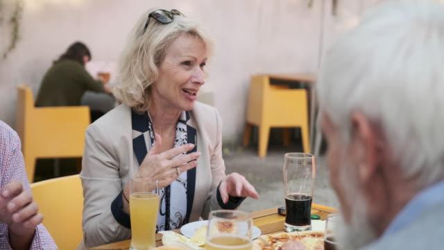 stockvideo's en b-roll-footage met senior vrienden genieten van ambachtelijke bieren en pizza in cafe - 70 79 jaar