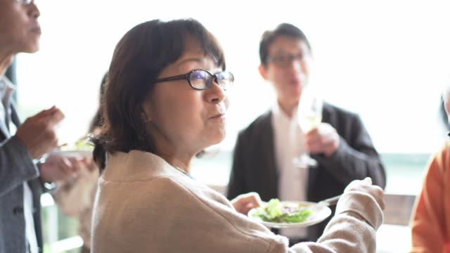 senior friends enjoying retirement party in cafe - 談笑する点の映像素材/bロール