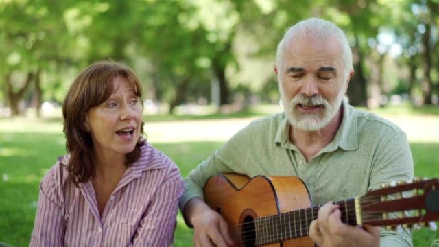 amici anziani che si godono la musica durante un picnic - hobby video stock e b–roll