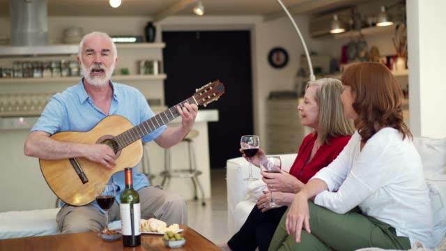 先輩の友達は家で飲み物を飲む - アコースティックギター点の映像素材/bロール