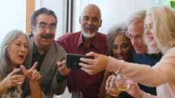 Senior friends looking at smart phone in party
