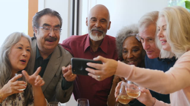 senior friends looking at smart phone in party - diversity stock videos & royalty-free footage