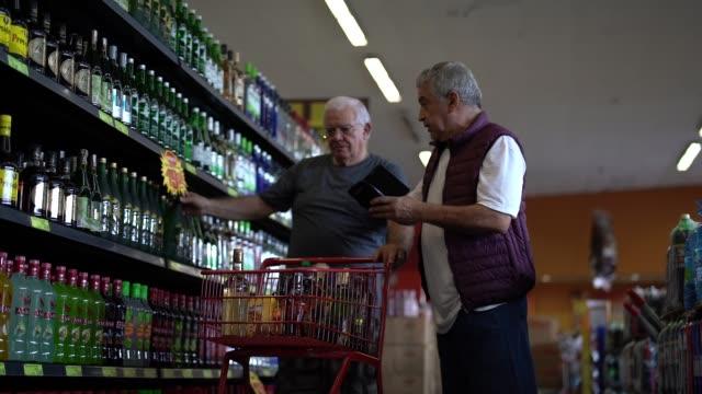vidéos et rushes de amis principaux sélectionnant quelques boissons au supermarché - alcool