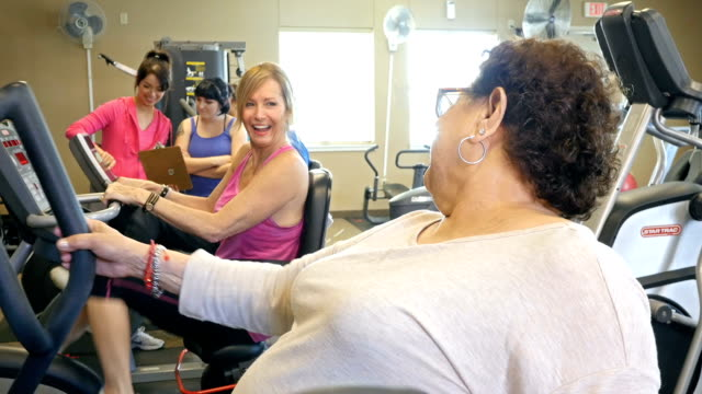 Senior friends talk while working out in gym