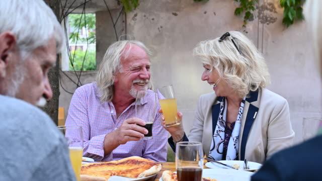 stockvideo's en b-roll-footage met hogere vrienden die en met bieren bij koffie bij koffie spreken en roosteren - 70 79 jaar
