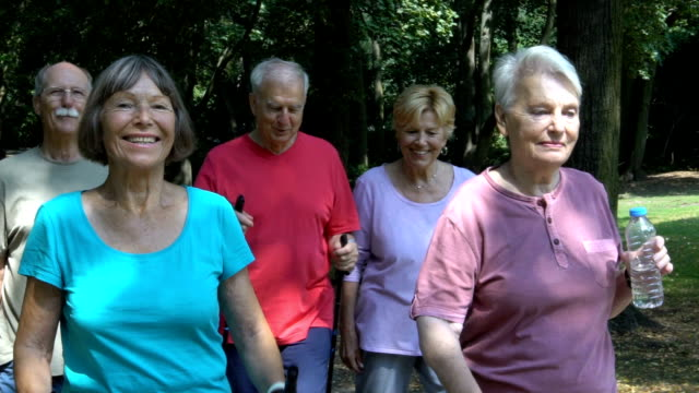 senior friends talking while walking at park - racewalking stock videos and b-roll footage