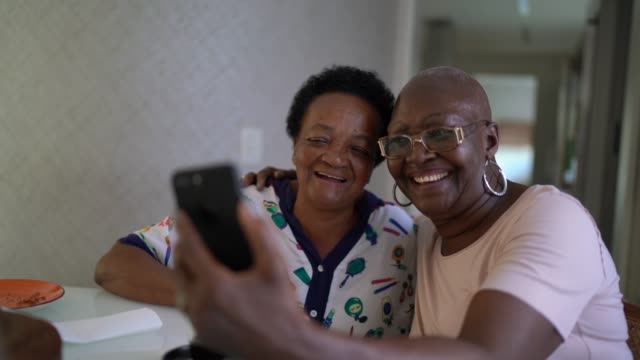vídeos de stock e filmes b-roll de senior friends women doing a video call using smartphone - afro