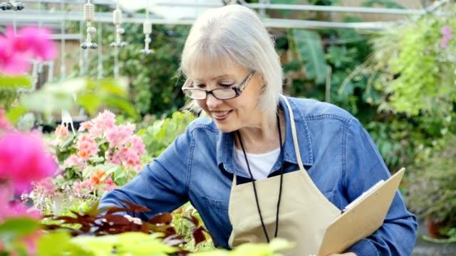 Senior garden center employee checks plant inventory