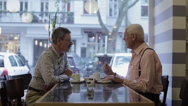 vidéos et rushes de senior gay couple eating breakfast in a hotel - gay man
