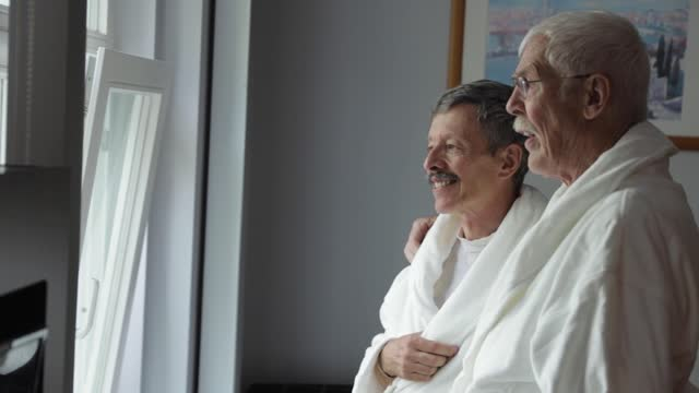 senior gay couple relaxing in bathrobes in hotel suite - bathrobe stock videos & royalty-free footage