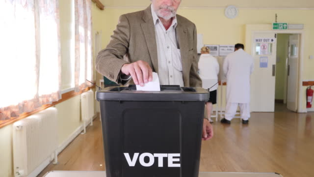 4K: Senior gentleman Putting Vote in Ballot Box at the Election - Voting at Polling Station