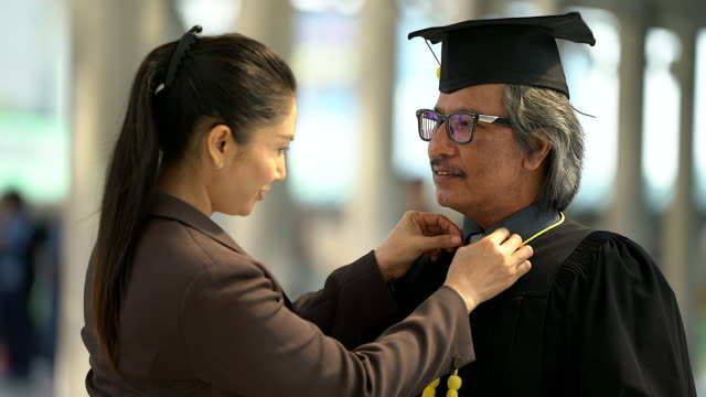 senior graduated student and his wife in cap gown preparing for graduated ceremony. - graduation stock videos and b-roll footage