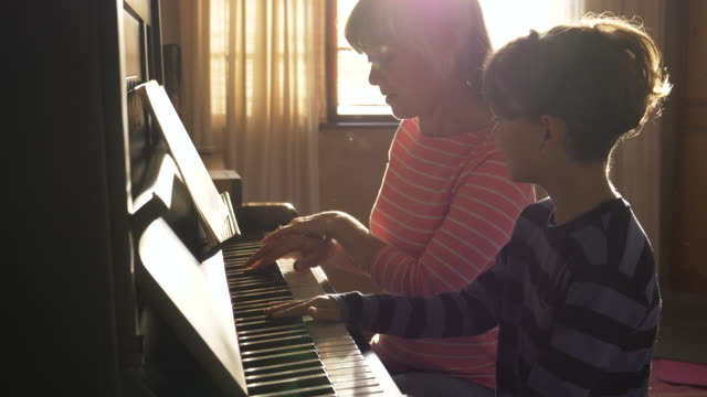 senior grandmother teaching her grandson to play the piano - piano stock videos & royalty-free footage