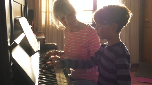 senior grandmother teaching her grandson to play the piano - hobbies stock videos & royalty-free footage