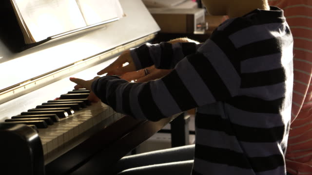 vídeos de stock e filmes b-roll de senior grandmother teaching her grandson to play the piano - pianista