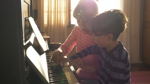 Senior grandmother teaching her grandson to play the piano
