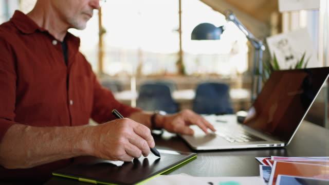 senior graphic designer creating art in his home office studio - disegnatore grafico video stock e b–roll
