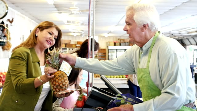 Senior grocer assists mid-adult Hispanic customer at check-out