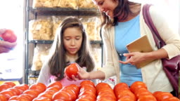 Senior grocer helps Hispanic mother and daughter pick out tomatoes at produce market