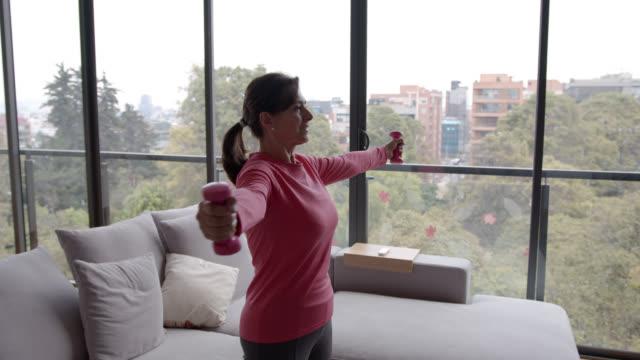 vídeos y material grabado en eventos de stock de mujer feliz de la tercera edad en casa ejercitando sus brazos con pesas libres - actividades y técnicas de relajación