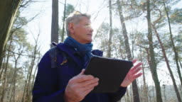 Senior hiker using digital tablet in forest